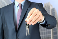 Cropped image of estate agent giving house keys. Outdoors Stock Images