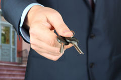 Cropped image of estate agent giving house keys. Outside Royalty Free Stock Photos