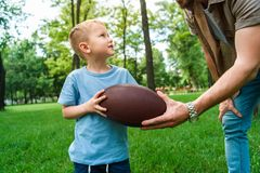 cropped image of father giving american football ball to son
