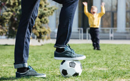 Cropped image of a father playing football with his son. Cropped image of a father playing football with his little son outdoors stock images