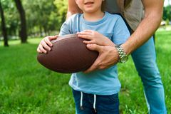 Cropped image of father and son holding american football ball. At park stock photography