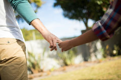 Cropped image of father and son holding hands. While standing in yard Stock Photography