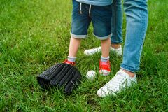 Cropped image of father and son standing on grass near baseball ball. And glove royalty free stock photography