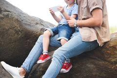 Cropped image of father and son using smartphone on stones. At park royalty free stock photo