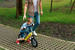 Cropped image of father supporting son while he riding bicycle. At park royalty free stock photo