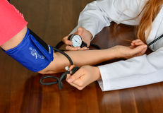 Cropped image of Female doctor checking blood pressure of patient at table. Stock Image Royalty Free Stock Photos