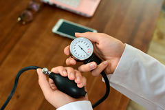 Cropped image of Female doctor checking blood pressure of patient at table. Stock Image Royalty Free Stock Photography