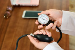 Cropped image of Female doctor checking blood pressure of patient at table. Stock Image Stock Photo
