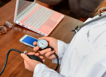 Cropped image of Female doctor checking blood pressure of patient at table. Stock Image Royalty Free Stock Image