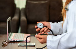 Cropped image of Female doctor checking blood pressure of patient at table. Stock Image Stock Photos