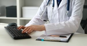 Cropped image of female doctor typing on keyboard . Cropped image of female doctor typing on keyboard stock video