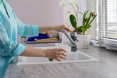 Cropped image of female hands with a Cup pours filtered tap water in the kitchen.  royalty free stock image