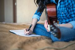 Cropped image of female hands writing in a notebook with an acoustic guitar.  Stock Images