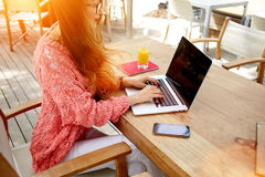 Cropped image of a female keyboarding on laptop computer with copy space screen while sitting in cafe outdoors, Royalty Free Stock Images