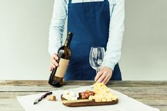 Cropped image of female sommelier holding bottle of white wine. And empty glass stock image
