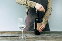 Cropped image of Female Sommelier opening the bottle of. Red wine stock photography