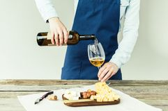 Cropped image of Female sommelier pouring white wine. Into glass royalty free stock photos