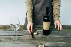 Cropped image of Female sommelier standing with open bottle of. Red wine stock photo