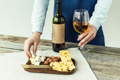 Cropped image of female sommelier taking glass of white wine and piece. Of cheese royalty free stock images