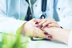 Cropped image of female therapist holding patient`s hands during the consultation. Medical ethics and trust concept. Cropped image of female therapist holding royalty free stock image