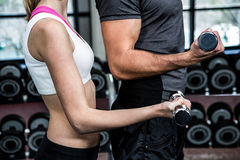 Cropped image of fit couple lifting dumbbells Royalty Free Stock Images