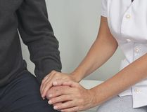 Female health care worker offering comfort to distressed patient. Cropped image focusing on female therapist holding male client`s hand offering comfort royalty free stock image
