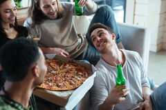 Cropped image of four friends sitting with pizza Stock Image