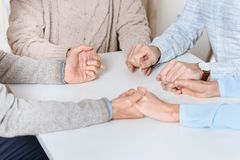 Cropped image of friends mily sitting at table and holding hands of each other while praying royalty free stock image