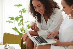 Cheerful women watching videos. Cropped image of friends watching something interesting on laptop Stock Image