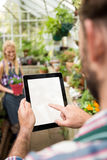 Cropped image of gardener using tablet at greenhouse. Cropped image of male gardener using tablet at greenhouse Stock Photo