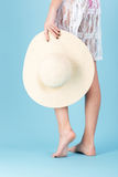 Cropped image of a girl holding beach hat over blue Royalty Free Stock Image