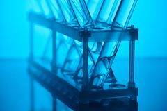 Glass tubes with liquid on stand in laboratory on blue stock images