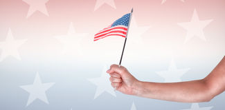 Cropped image of hand holding American flag. Against starry background Royalty Free Stock Photo
