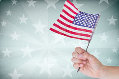 Cropped image of hand holding American flag. Against starry background Stock Photography