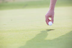 Cropped image of hand holding golf ball over cup Royalty Free Stock Photography