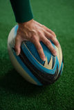 Cropped image of hand holding rugby ball. On playing field royalty free stock photo