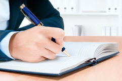 Cropped image of hand of young woman taking notes Stock Images