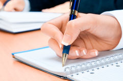 Cropped image of hand of young woman taking notes. Office and business Royalty Free Stock Images