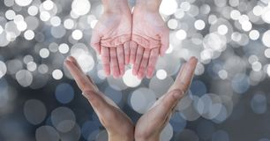 Cropped image of hands against glowing bokeh Royalty Free Stock Photos