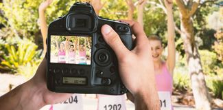 Composite image of cropped image of hands holding camera Royalty Free Stock Photo