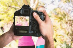 Composite image of cropped image of hands holding camera Royalty Free Stock Images
