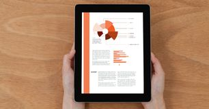 Cropped image of hands holding digital tablet with chart and information on screen Stock Photography