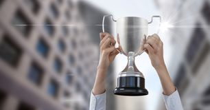 Cropped image of hands holding trophy against buildings Stock Image