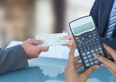 Cropped image of hands using calculator against business people exchanging currencies. Digital composite of Cropped image of hands using calculator against royalty free stock photos