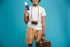 Cropped image of handsome young african man. Tourist isolated over blue wall background holding tickets with passport and suitcase Stock Photography