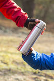 Cropped image of hikers holding insulated coffee container in forest Royalty Free Stock Photo