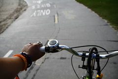 Cropped Image Of Human Hand Riding Bicycle With Road Marking Royalty Free Stock Photography