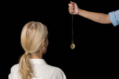 Cropped image of hypnotherapist holding pendulum by woman Stock Photography