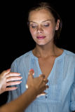 Cropped image of hypnotist hypnotizing woman. Against black background Stock Images