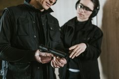 Cropped image of instructor showing gun to female client. In shooting gallery royalty free stock images